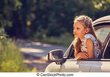 Fun happy enjoying traveling kid girl looking from the car window with open mouth on summer bright green nature background. Closeup summer portrait. Little driver. Kids safety.