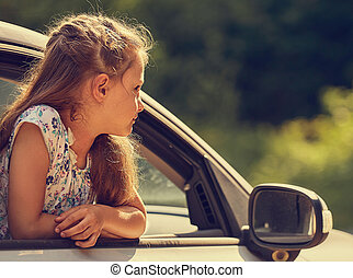 Fun happy enjoying traveling kid girl looking from the car window with open mouth on summer bright green nature background. summer portrait. Little driver. Kids safety.