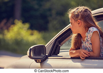 Fun happy enjoying traveling kid girl looking from the car window with open mouth on summer bright green nature background. toned summer portrait. Little driver. Kids safety.