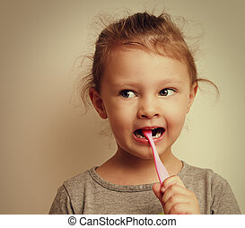 Fun happy kid girl brushing the teeth and looking. Vintage portrait