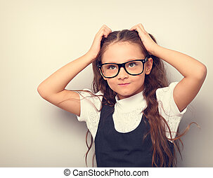 Fun happy pupil kid girl in eyeglasses scratching the head two hands and looking up on empty copy space background. Toned color portrait