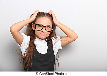Fun happy pupil kid girl in eyeglasses scratching the head two hands and looking up on empty copy space background.