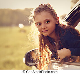 Fun happy traveling kid girl looking from the car window on summer bright green nature background. Toned closeup portrait
