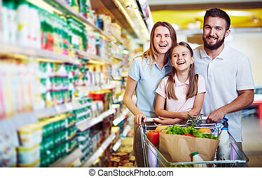 Fun in supermarket - Ecstatic family with shopping cart with...