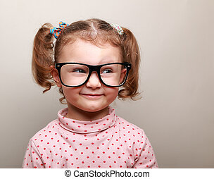 Fun kid girl in glasses looking on empty copy space