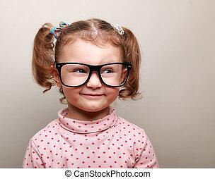 Fun kid girl in glasses looking on empty copy space