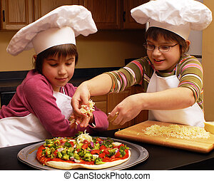 Elementary-aged sisters in chef's hats spreading toppings on a veggie pizza.