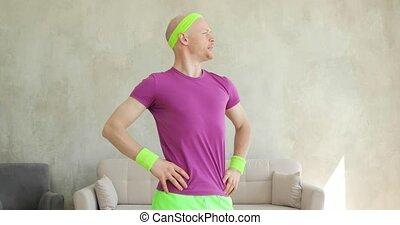 Fun man in sportswear pretends to be macho looking at camera...