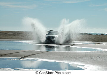 Fun on the beach - A four-wheel-drive ploughs through the...