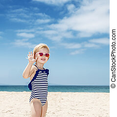 Happy girl in striped swimsuit on a white beach handwaving