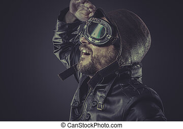 fun, pilot dressed in vintage style leather cap and goggles