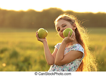 Fun playing beautiful kid girl with long hair joying and biting green apples on summer bright background. Closeup bright portrait