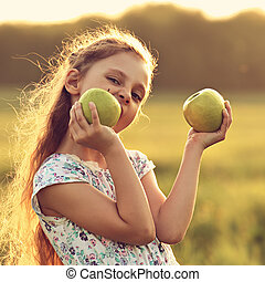 Fun playing beautiful kid girl with long hair joying and biting green apples on summer bright background. Closeup toned bright portrait