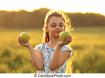 Fun playing beautiful kid girl with long hair joying and looking on green apples on summer bright background. Closeup portrait