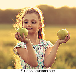 Fun playing beautiful kid girl with long hair joying and looking on green apples on summer bright background. Closeup toned color portrait