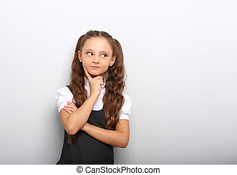 Fun pupil girl school uniform thinking and looking up on blue background with empty copy space