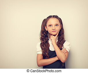 Fun pupil girl school uniform thinking and looking up on blue background with empty copy spase. Vintage portrait