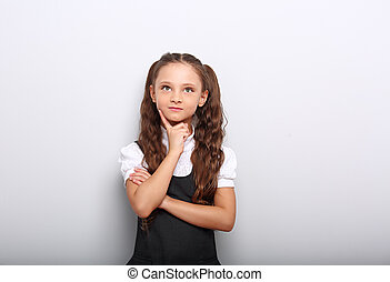 Fun pupil girl school uniform thinking and looking up on blue background with empty copy spase