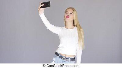 Fun sexy young woman posing for a selfie