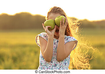 Fun surprising beautiful kid girl with long hair playing with green apples on summer bright background. Closeup portrait