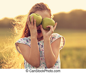 Fun surprising beautiful kid girl with long hair playing with green apples on summer bright background. Closeup toned color portrait