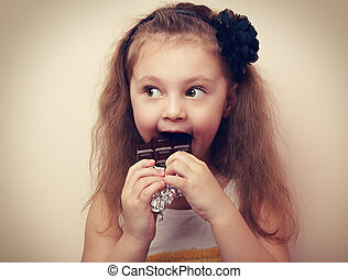 Fun surprising kid girl eating dark chocolate. Vintage...