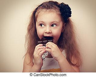 Fun surprising kid girl eating dark chocolate. Vintage...