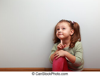 Fun thinking kid girl sitting in pink jeans and looking up