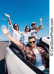 Fun travel. Group of young happy people enjoying road trip in their white convertible and raising their arms up