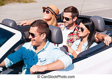 Fun travel. Top view of young happy people enjoying road trip in their white convertible