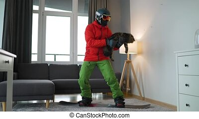 Fun video. Man dressed as a snowboarder rides a snowboard on a carpet in a cozy room. He holds a fluffy cat in his arms. Waiting for the start of the winter ski season