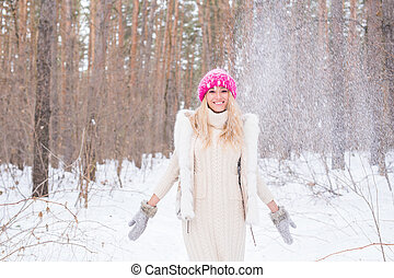 Fun, winter and people concept - Attractive woman dressed in white coat throwing snow.