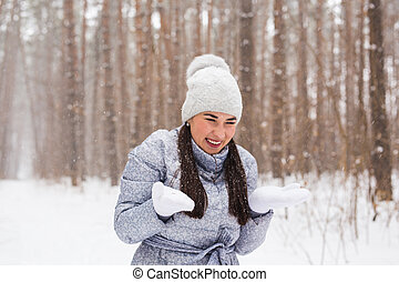 Fun, winter and people concept - Attractive young woman dressed in coat throwing snow.