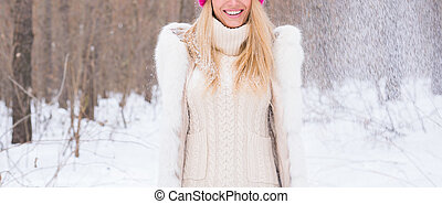 Fun, winter and people concept - Close up of young woman dressed in coat throwing snow.
