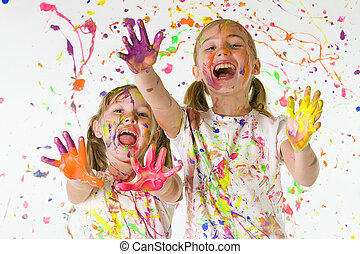 two girls having fun with splattered paint