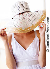fun woman covering her face with hat
