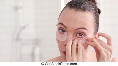fun woman take of facial eye patch in her bathroom