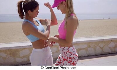Fun young woman showing off her biceps to an attractive...