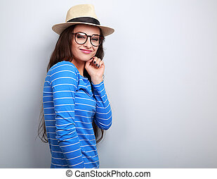 Fun young woman with thinking look in glasses and straw hat on blue background