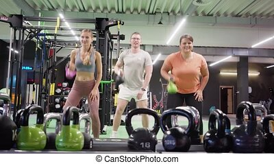 Functional training with dumbbells in the gym done by two women and a man