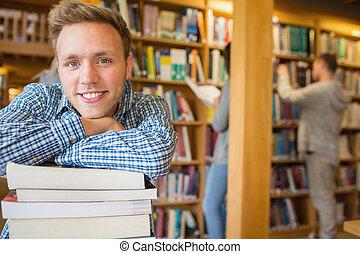 fundo, biblioteca, enquanto, livros, estudante universitário, outros, retrato, sorrindo, macho, pilha
