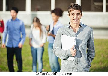 fundo, estudantes, livros, segurando, campus, homem