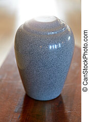 cremation urn on table - funeral and mourning concept -...