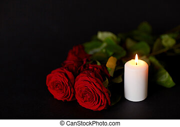 red roses and burning candle over black background - funeral...