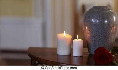 funerary urn and candles on table burning indoors - funeral,...