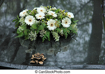 Funeral flowers on a tomb - White funeral flowers on a grey...