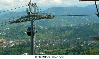 Funicular cable car in the summer in the mountains. Cabs passes a beautiful cloudy sky