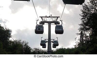 Funicular - Ski lift chairs on bright day over the clouds,...