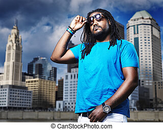 funky african man with sunglasses in front of city