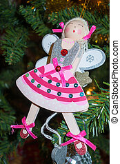 Funky angel decoration hanging on a christmas tree